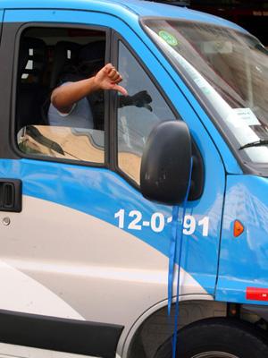 Policiais militares, em um carro da Unidade de Polícia Pacificadora (UPP) São João (com uma fita azul de protesto no carro), fazem sinal de negativo (Foto: Guilherme Pinto / Agência O Globo)
