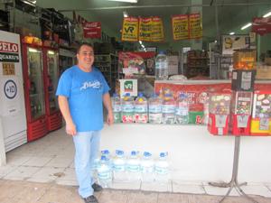 Sidnei mostra o que restou do estoque de água de seu mercado (Foto: Juliana Cardilli/G1)