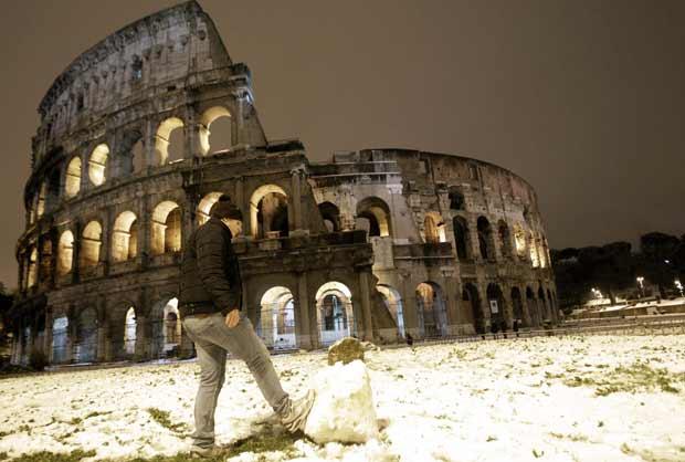 Garoto brinca com bola de neve em frente ao prédio do Coliseu, em Roma, após nevasca que 'branqueou' a capital da Itália na madrugada deste sábado (11) (Foto: AP)