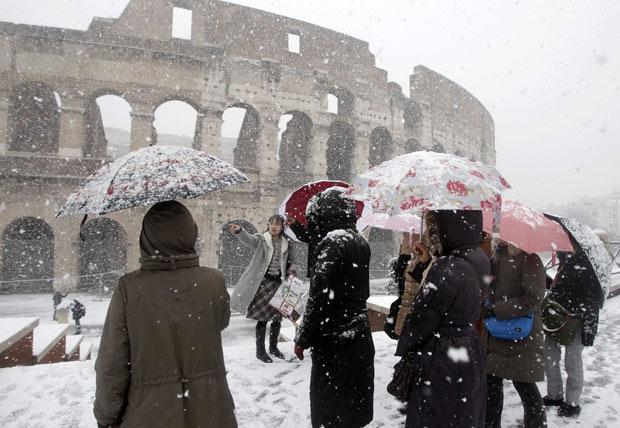 Grupo de turistas se protege da nevasca enquanto observa o Coliseu coberto de neve, neste sábado (11) (Foto: Riccardo De luca / AP)