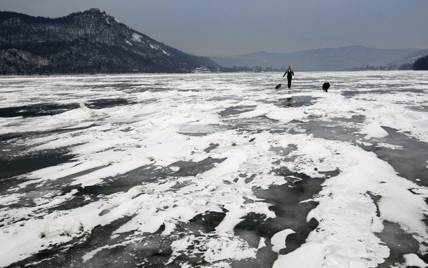 Homem anda com seus cachorros em trecho congelado do rio Danúbio neste sábado (11), em Nagymaros, na Hungria (Foto: Laszlo Balogh / Reuters)