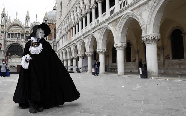 Com máscaras e trajes clássicos, foliões enfrentam o frio para desfilar pelas ruas de Veneza (Foto: Stefano Rellandini / Reuters)