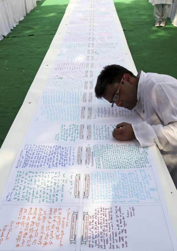 Estudante escreve sua mensagem em uma 'Carta para Deus' de 122 metros de comprimento, neste domingo (12), na cidade indiana de Chandigarh. Mais de 1.500 fiéis de várias religiões deixaram mensagens para seus deuses, segundo a organização espiritual Brahma Kumaris  (Foto: Ajay Verma/Reuters)