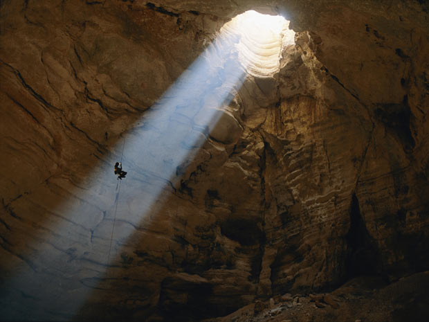 Um estudioso de cavernas desce as profundezas de Majlis al Jin, no Omã, iluminado por um raio de luz que confere à foto um tom sobrenatural. (Foto: STEPHEN ALVAREZ / NATIONAL GEOGRAPHIC STOCK / CATERS NEWS)