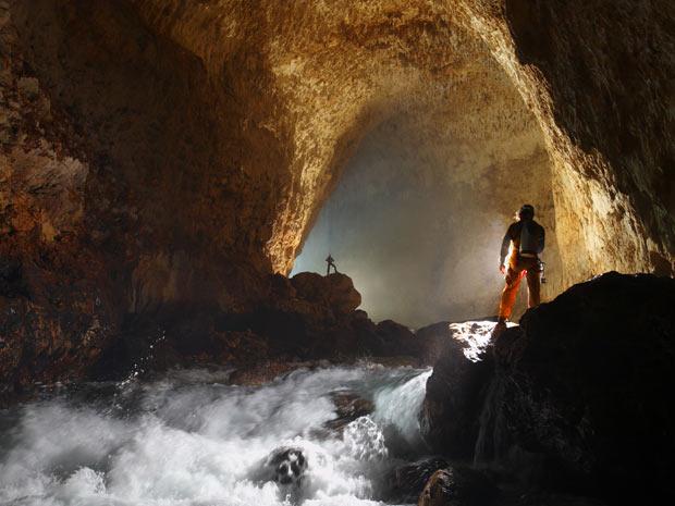 Para realizar seus estudos, os exploradores precisam vencer desafios como os rios subterrâneos, tais e quais este que corre na entrada da caverna de Ora, em Papua Nova Guiné. (Foto: STEPHEN ALVAREZ / NATIONAL GEOGRAPHIC STOCK / CATERS NEWS)