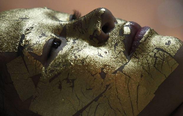 Mulher faz tratamento com máscara facial de ouro. (Foto: Kham/Reuters)