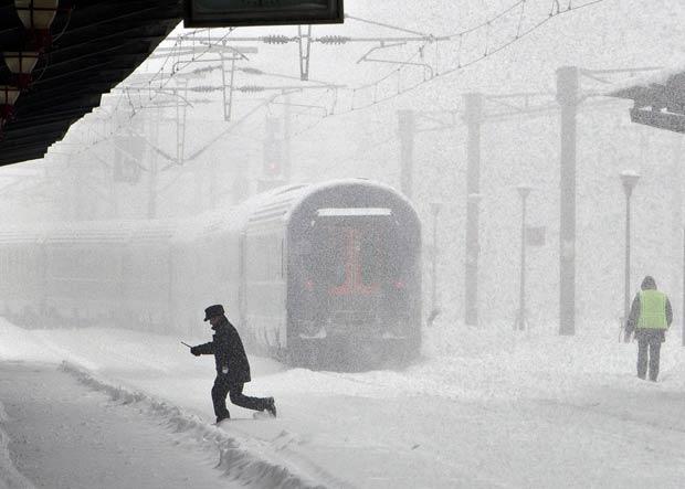 Trem parte de estação com trilhos cobertos pela neve nesta segunda-feira (13) em Bucareste, capital da Romênia (Foto: AP)