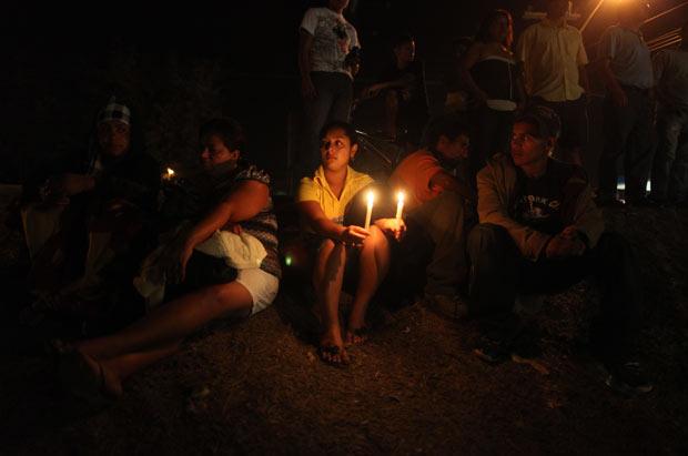Parentes de presos fazem vigília em frente à cadeia de Comayagua, centro de Honduras, na noite desta quarta-feira (15) (Foto: AP)