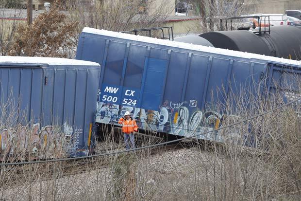 Resgatista observa vagões que saíram dos trilhos nesta sexta-feira (17) em Arlington, no estado americano do Texas. Um tanque com xarope de milho e outros vagões de carga tombaram, mas ninguém se machucou (Foto: AP)