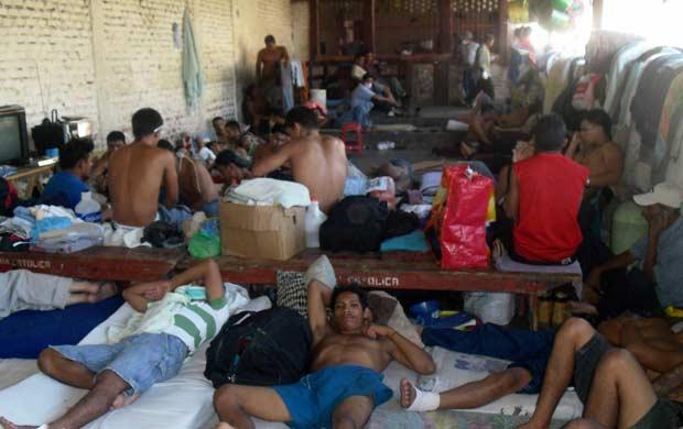 Presos sobreviventes do incêndio amontoados nesta sexta-feira (17) no que sobrou da prisão de Comayagua, no centro de Honduras (Foto: AP)