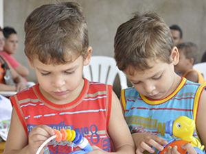 Irmãos Marcus e Matheus se divertem com brinquedos (Foto: Iara Vilela / G1)