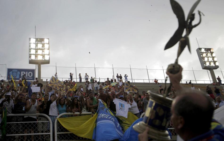 Integrantes da escola de samba Unidos da Tijuca comemoram junto com a diretoria da agremiação e com o troféu de campeã do carnaval de 2012.