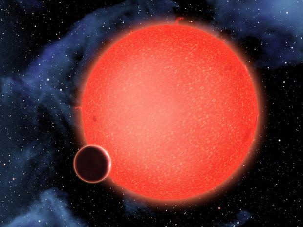 Imagem divulgada pela Nasa mostra o planeta orbitando uma estrela vermelha há 40 anos-luz da Terra.  (Foto: AFP Photo / Nasa / ESA / D.Aguilar)