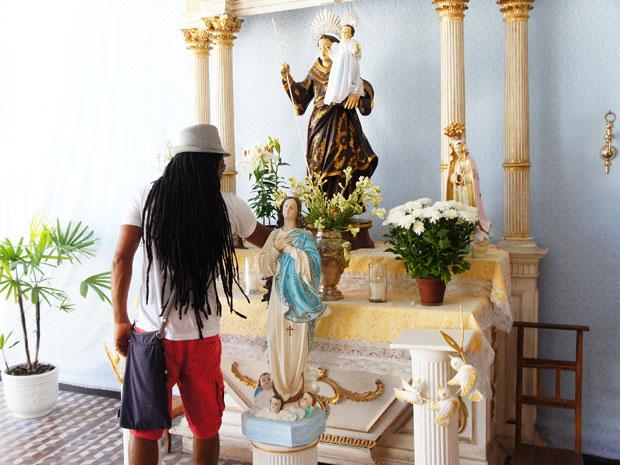 Carlinhos Brown ora diante de imagem de Santo Antônio no Candyall Guetho Square antes de viajar para os EUA (Foto: Glauco Araújo/G1)