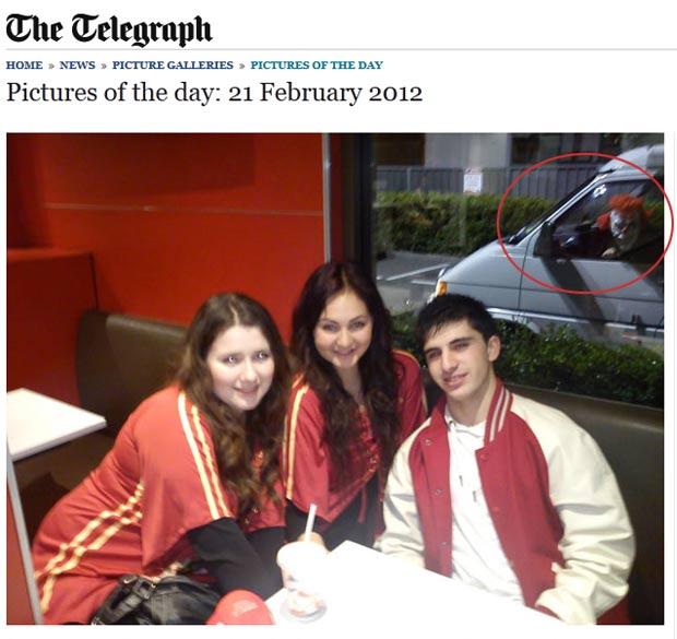 Foto de amigos flagra palhaço assustador ao fundo. (Foto: Reprodução/Daily Telegraph)