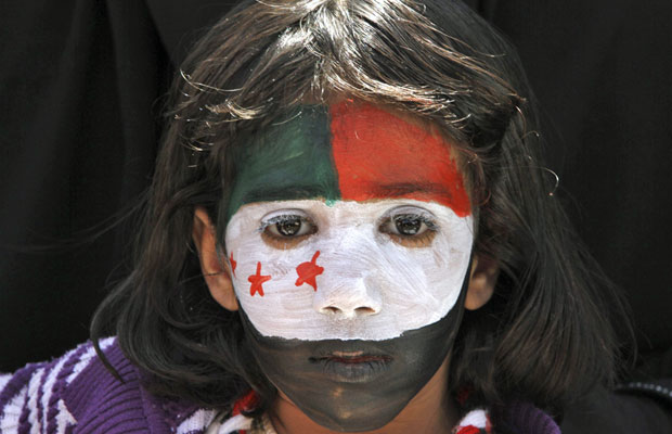 Menina tem rosto pintado com as cores da bandeira da Síria em protesto contra a repressão em Sanaa (Foto: Mohamad Al Sayaghi/Reuters)