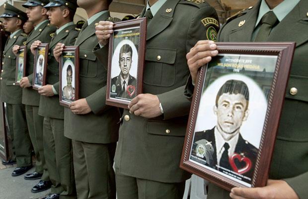 Policiais colombianos seguram imagens de colegas sequestrados pelas Farc em protesto no dia 23 de fevereiro, em Bogotá (Foto: Fernando Vergara)