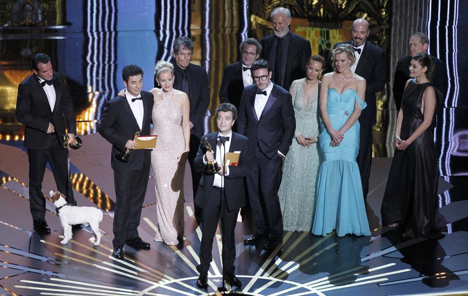 Com elenco e equipe de 'O artista' ao fundo, produtor Thomas Langmann discursa no Oscar após longa vencer o prêmio de melhor filme.