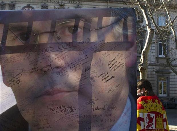 homem enrolado em uma bandeira dos republicanos caminha próximo a uma imagem do juiz espanhol Baltasar Garzón durante uma manifestação de apoio do lado de fora da Suprema Corte, em Madri, no dia 12 deste mês (Foto: Sergio Perez/Reuters)