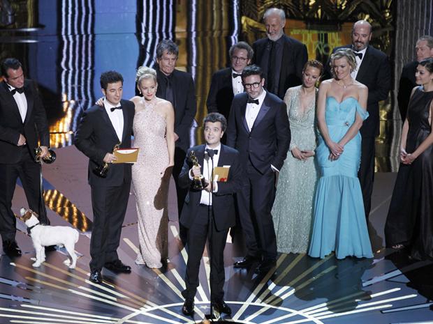 Com elenco e equipe de 'O artista' ao fundo, produtor Thomas Langmann discursa no Oscar após longa vencer o prêmio de melhor filme (Foto: Gary Hershorn/Reuters)