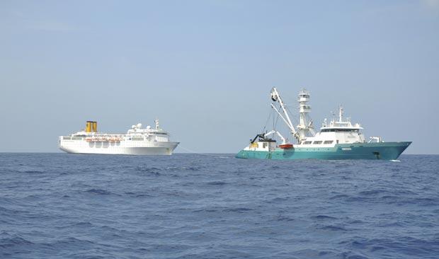 Foto tirada por tripulante de pesqueiro francês e divulgada pelo governo das Ilhas Reunião mostra o Costa Allegra (à esquerda) sendo rebocado pelo pesqueiro francês Trevignon, no Oceano Índico, nesta terça-feira (28) (Foto: AP)