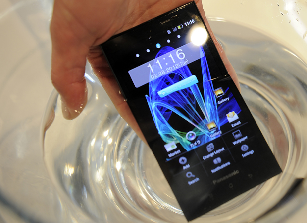 Homem mergulha o Eluga em um copo de água durante demonstração no Mobile World Congress. (Foto: Luis Gene/France Presse)