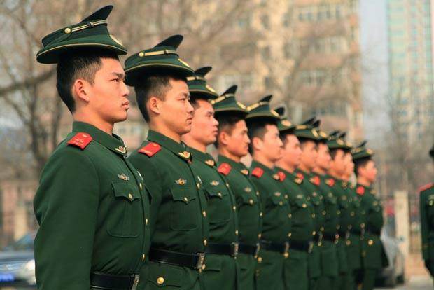 Policiais chineses usaram os quepes de cabeça para baixo. (Foto: AFP)