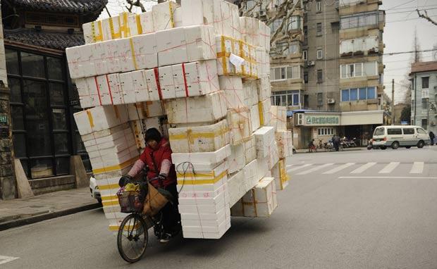 Mulher foi flagrada com um triciclo supercarregado com caixas de isopor. (Foto: Peter Parks/AFP)