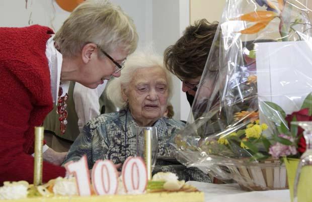 A francesa MArthe Odile Charton, de 100 anos, ganha flores após soprar as velinhas de seu 25º 'aniversário', neste dia 29 de fevereiro, na casa de retiro em que mora em Colmar. Odile nasceu em 29 de fevereiro de 1912 em Ingersheim e só celebrou 25 aniversários no dia 'correto' (Foto: AFP)