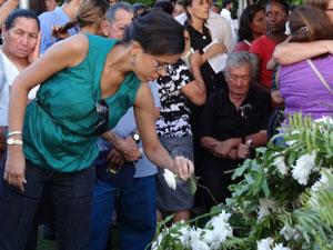 Fiel coloca flor no monte do coroas acima do túmulo do bispo e sua esposa (Foto: Luna Markman/G1)