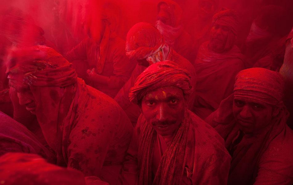 Pessoas são cobertas por pó colorido durante a celebração do tradicional festival Holi, no templo Radha Rani, na cidade indiana de Barsana.