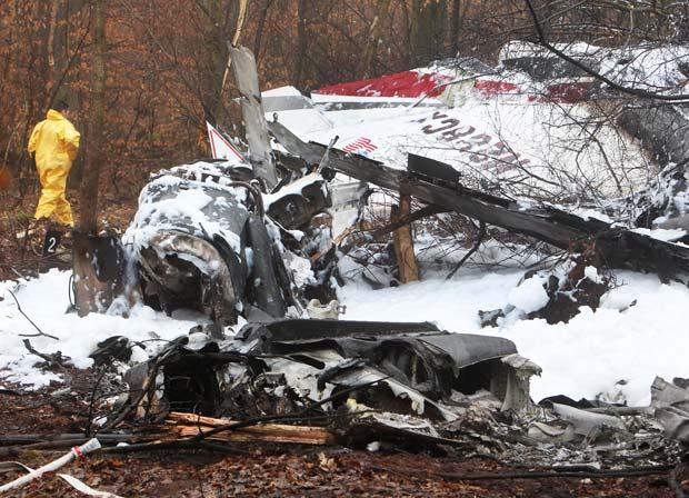 Destroços de avião de pequeno porte caído em floresta na cidade alemã de Egelsbach, próximo a Frankfurt, nesta sexta-feira (2). A polícia diz que o avião, com cinco pessoas a bordo, caiu e pegou fogo na noite de quinta ao tentar pousar. Pelo menos três corpos já foram encontrados (Foto: AP)