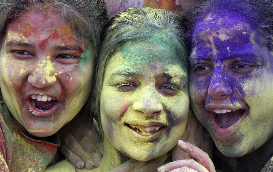 Jovens estudantes se divertem cobertas de pó colorido em Chandigarh.