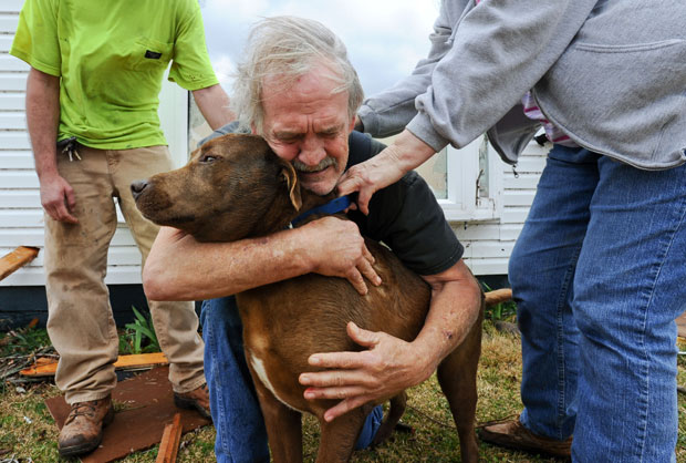 Emocionado, Greg Cook abraça a cadela, Coco, encontrada no interior da casa destruída em East Limestone (Foto: AP/Gary Cosby Jr./The Decatur Daily)