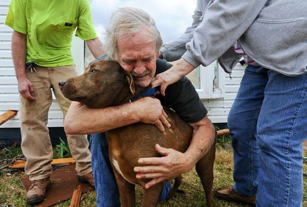 Emocionado, Greg Cook abraça a cadela, Coco, encontrada no interior da casa destruída em East Limestone (Foto: AP/Gary Cosby Jr./The Decatur Daily)