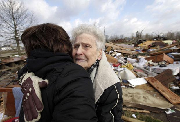 Vizinhas se abraçam em cenário de destruição num bairro residencial de Marysville, Indiana, neste sábado (3) (Foto: AP)