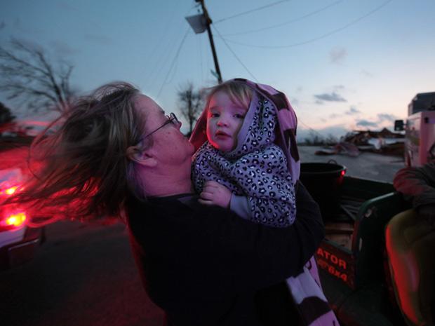 Moradora protege criança após passagem de tornado na cidade de Metro Piner, no Kentucky.  (Foto: AP)