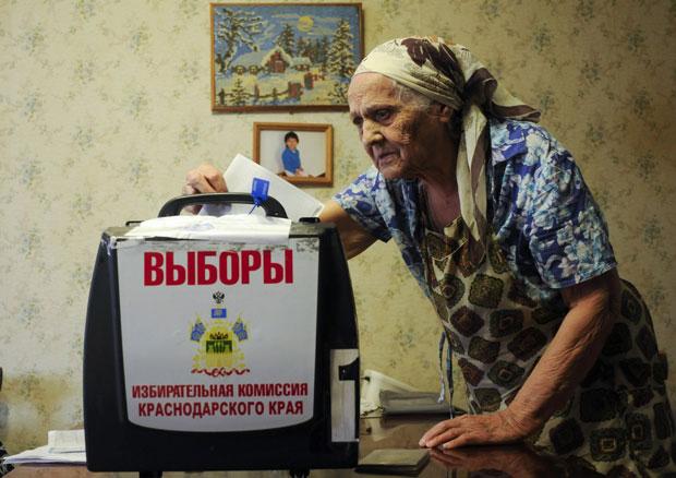 Mulher deposita seu voto em urna levada até sua casa em Krasnodar, no sul da Rússia (Foto: Sergei Karpov/Reuters)