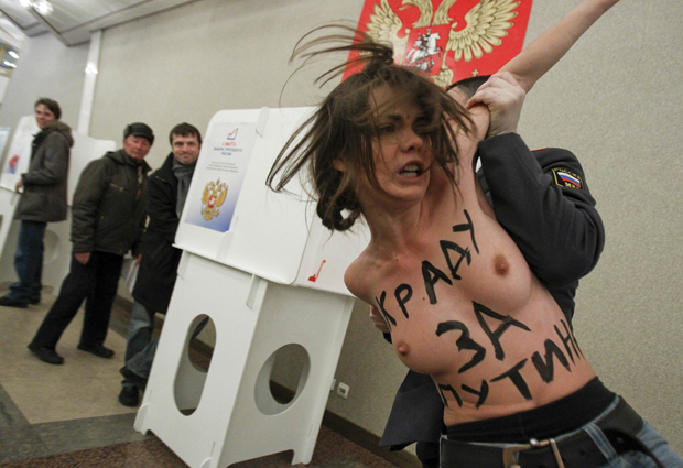 Três manifestantes do grupo ucraniano Femen, conhecido por seu protesto contra violações aos direitos humanos reunindo mulheres seminuas, é detida em seção eleitoral em Moscou, na Rússia, na manhã deste domingo (4) (Foto: Denis Sinyakov/Reuters)