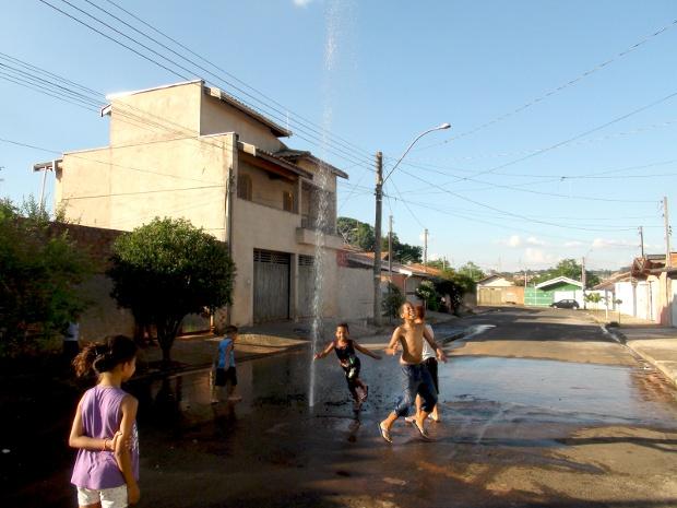 Crianças brincam em chafariz formado depois de buraco em encanamento (Foto: Nikolas Capp/ G1)