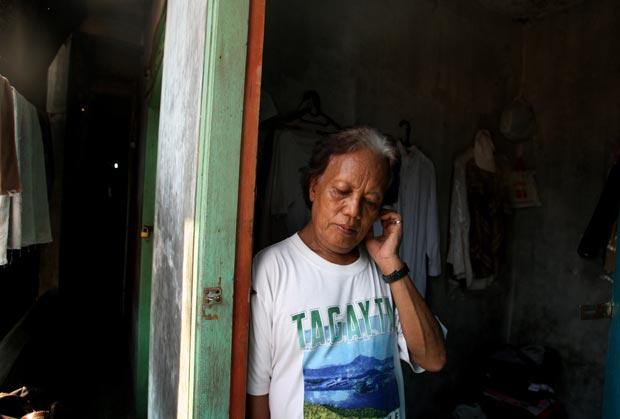 Evie, ou Turdi, ex-babá do presidente americano Barack Obama, em 27 de janeiro na entrada de seu quarto em um cortiço de Jacarta, na Indonésia. Evie nasceu homem, mas se identifica com o gênero feminino e afirma ter passado por uma vida de agressões e pre (Foto: Dita Alangkara/AP)
