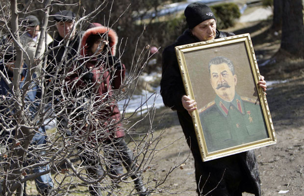 Mulher carrega retrato do ex-ditador soviético Josef Stalin em sua cidade natal, Gori. Dezenas de comunistas georgianos se reuniram nesta segunda para relembrar o 59º aniversário de sua morte   (Foto: David Mdzinarishvili/Reuters)