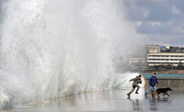 Dois adolescentes quase foram atingidos no sábado (3) por uma onda em Sebastopol, na Ucrânia. Os dois garotos observavam o Mar Negro quando uma onda mais forte atingiu o local em que eles estavam. (Foto: Genya Savilov/AFP)