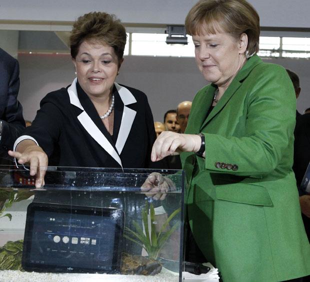 Dilma e Merkel sorriem após mergulharem o tablet da Fujitsu dentro da água. O aparelho, segundo a fabricante, pode ser usado em uma banheira ou piscina sem problemas. Ele roda sistema Android 3.2, tem tela de 10,1 polegadas e sintoniza canais de TV digita (Foto: Fabrizio Bensch/Reuters)