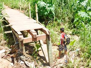 Estudante atravessou córrego em Cuiabá (Foto: Marcelo Ferraz / G1)