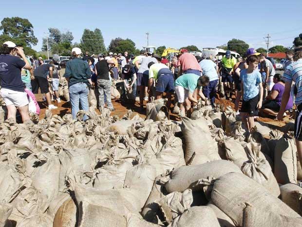 Moradores de Wagga Wagga, na Austrália, erguem diques para conter inundações causadas pela cheia do Rio Murrumbidgee. (Foto: Daniel Munoz / Reuters)