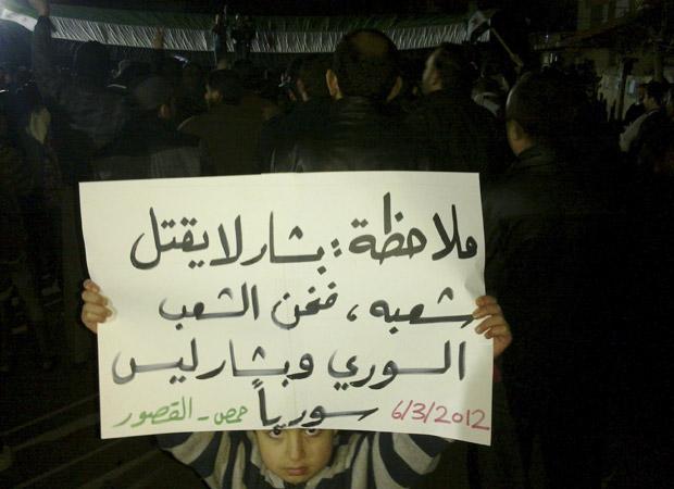 Garoto mostra cartaz com críticas ao presidente síria Bashar al Assad durante protestos nesta terça-feira (6) em Homs (Foto: Reuters)