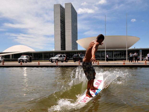 Manifestante surfa nos espelhos d´água do Congresso durante protesto contra o Código Florestal (Foto: Pedro Ladeira / AFP Photo)