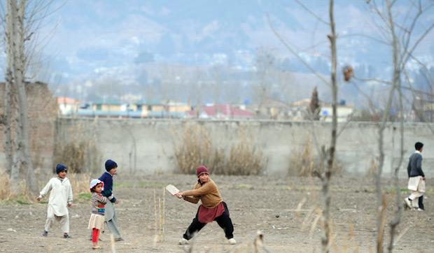 Crianças paquistanesas jogam críquete perto de muro da casa onde foi morto Osama bin Laden, no Paquistão (Foto: Aamir Qureshi / AFP)
