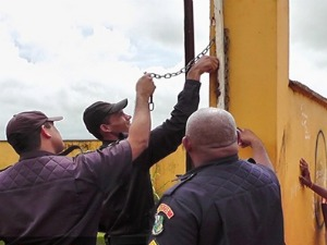 Policiais abrem cadeados colocados por alunos. (Foto: Uasley Werneck/ Agência da Notícia)